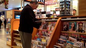 Close up man choosing magazine to buy at newspaper booth Stock Images