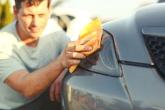 Close up of man cleaning car with microfiber cloth. Car detailing Royalty Free Stock Image