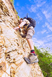 Close up of a man climbing up red rock Royalty Free Stock Photo