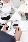 Close up of man with coffee and smart phone and his colleague Stock Photos