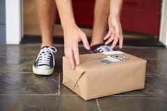 Close Up Of Man Collecting Parcel Delivery Outside Door Stock Photos