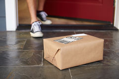 Close Up Of Man Collecting Parcel Delivery Outside Door Stock Image