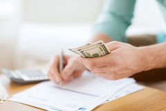 Close up of man counting money and making notes Royalty Free Stock Images