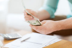 Close up of man counting money and making notes Royalty Free Stock Image