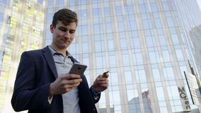 Close up of Man with credit card during shopping through internet using smart phone in city stock footage