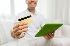 Close up of man with credit card and tablet pc Stock Photos