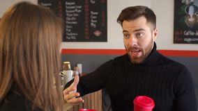 Close-up of a man with a Cup of coffee talking to his girlfriend in coffee shop. Close-up of a young man with a Cup of coffee cute talking to his girlfriend in stock footage