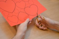Close-up of a man cutting hearts out of red paper according to a pattern with small golden scissors royalty free stock image