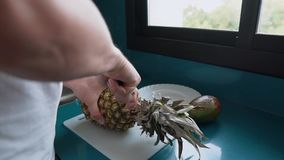 Man cuts fruit. Close-up of a man cutting pineapple on a board in home kitchen. Fresh healthy fruit. Eating healthy stock video footage