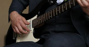 Man in dark outfit sitting and playing on beautiful guitar jazz music. Close up of man in dark outfit sitting and playing on beautiful guitar and listening stock video
