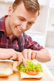 Close up of man decorating bread with lettuce Royalty Free Stock Photos