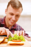 Close up of man decorating bread with lettuce Royalty Free Stock Images
