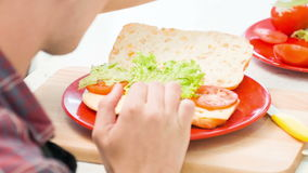 Close up of man decorating bread with lettuce and stock footage