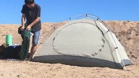 Tent dismantling process. Close up of a man is disassembling camping tent on the beach time lapse process stock video footage