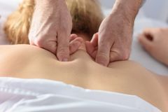 Close-up on the man doctor hands. Caucasian Woman Receiving Therapeutic Back Massage in medical office. stock photography
