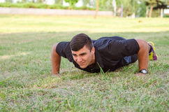 Close up of a man doing pushups on the grass with the horizon in the background. Stock Image