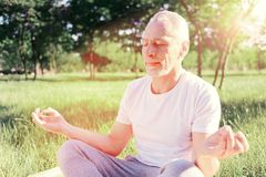 Close up of man doing yoga. Calmness. Close up of peaceful man keeping fingers together while sitting on the ground pad and doing yoga Stock Image
