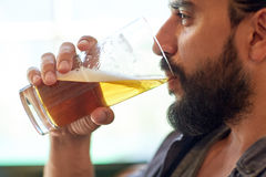 Close up of man drinking beer at bar or pub. People, drinks, alcohol and leisure concept - close up of young man drinking beer from glass at bar or pub Royalty Free Stock Image