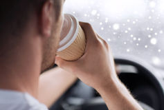 Close up of man drinking coffee while driving car Stock Images