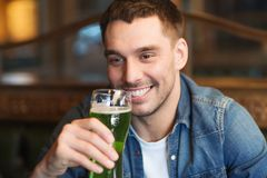 Close up of man drinking green beer at bar or pub. People, leisure and st patricks day concept - close up of happy young man drinking green beer at bar or pub Royalty Free Stock Images