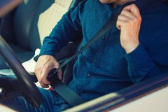 Close up man driver fastening seat belt. Guy seated behind the steering wheel testing his new car safety. Secure transportation and safe vehicle concept. Male royalty free stock image
