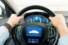 Close up of man driving car with icon on computer. Transport, business trip, technology and people concept - close up of male hands holding car wheel and driving Stock Image