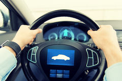 Close up of man driving car with icon on computer. Transport, business trip, technology and people concept - close up of male hands holding car wheel and driving Stock Photo