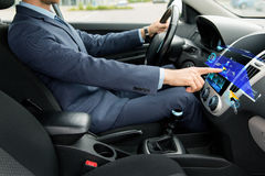 Close up of man driving car with navigation. Transport, business trip, navigation, technology and people concept - close up of young man in suit driving car and Stock Photography