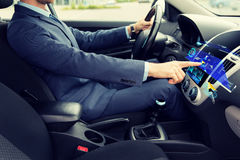 Close up of man driving car with navigation. Transport, business trip, navigation, technology and people concept - close up of young man in suit driving car and royalty free stock image