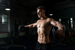 Close up of man with dumbbells exercising in gym Royalty Free Stock Photos