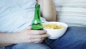 Close up of man eating chips and drinking beer stock video footage