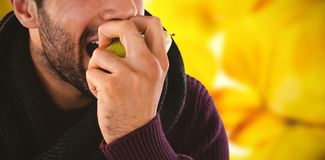 Composite image of close-up of man eating pear. Close-up of man eating pear against autumnal leaves against blurred plants Royalty Free Stock Images