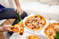 Close up of man eating pizza with beer at home Stock Photography