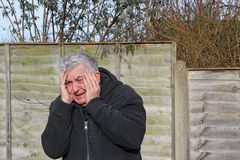 Close up of man experiencing a panic attack. A close up of a senior man with his hands to his face having a panic attack Stock Images