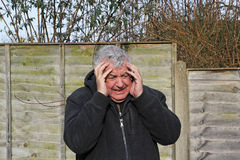 Close up of man experiencing a panic attack. A close up of a senior man with his hands to his face having a panic attack Stock Photos