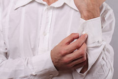 Close up of man fastening buttons on shirt sleeve. Businessman buttoning up white shirt. Groom preparing for wedding. Perfect whit Royalty Free Stock Image