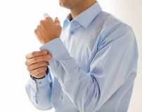 Close up of man fastening buttons on shirt sleeve Stock Images