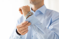 Close up of man fastening buttons on shirt sleeve Royalty Free Stock Image