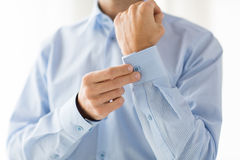 Close up of man fastening buttons on shirt sleeve Stock Photography