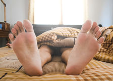 Close-up a man feet on bed in the morning Stock Photography