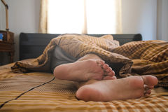 Close-up a man feet on bed in the morning Royalty Free Stock Images