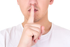 Close up of man with finger on lips asking for silence over whit Stock Photos