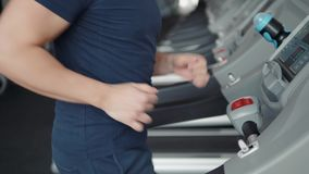 Close up of man finger pushing stop button on treadmill. Safety in gym, end of training. Close up of man finger pushing stop button on treadmill stock video