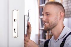Close-up Of A Man Fixing Door Lock. Close-up Of A Smiling Young Man Fixing Door Lock In House stock photography