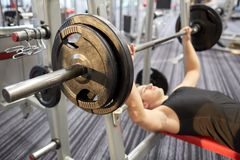 Close up of man flexing biceps with barbell in gym Stock Photography