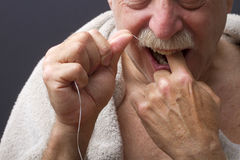 Close-Up of Man Flossing Teeth. Close-up of a man flossing his teeth,  on a black background Stock Images