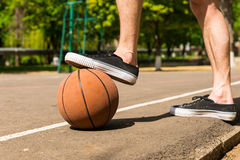 Close Up of Man with Foot on Basketball on Court Royalty Free Stock Image