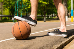 Close Up of Man with Foot on Basketball on Court Royalty Free Stock Images