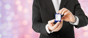 Close up of man with gift box and engagement ring. People, holidays, presents and proposal concept - close up of man with gift box and engagement ring over stock photos