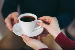 Man giving woman cup of coffee stock photo